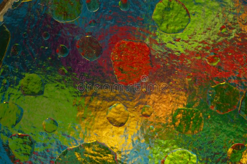 Colored objects through corrugated glass when mixing water and oil. Colored abstract background when mixing water and oil with upper side lighting, through stock image