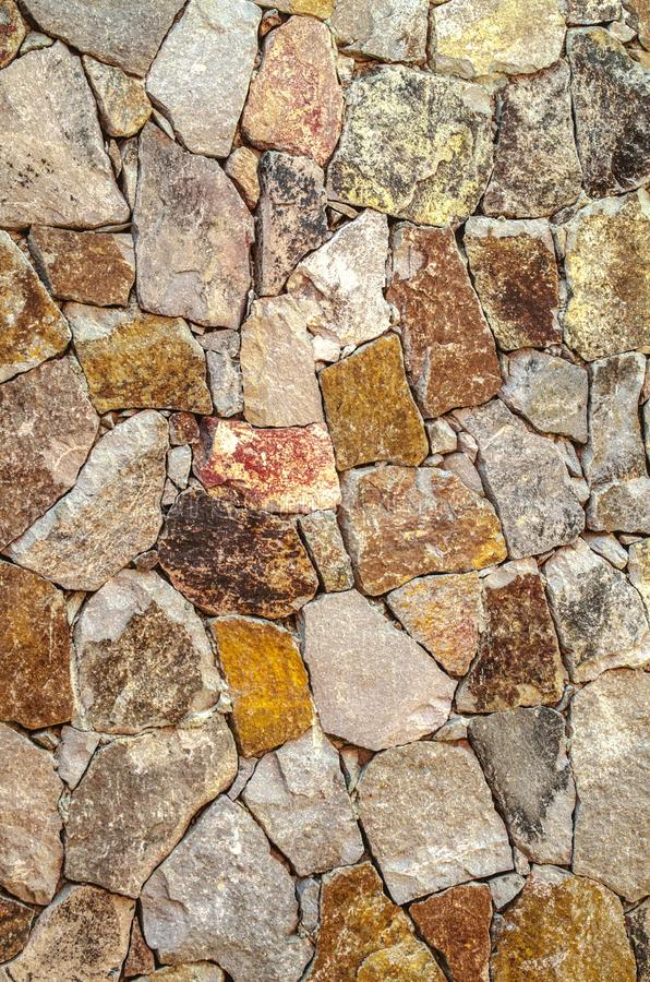 Colored background for the facade of the house in light yellow and pink shades of raw natural stone stock photo