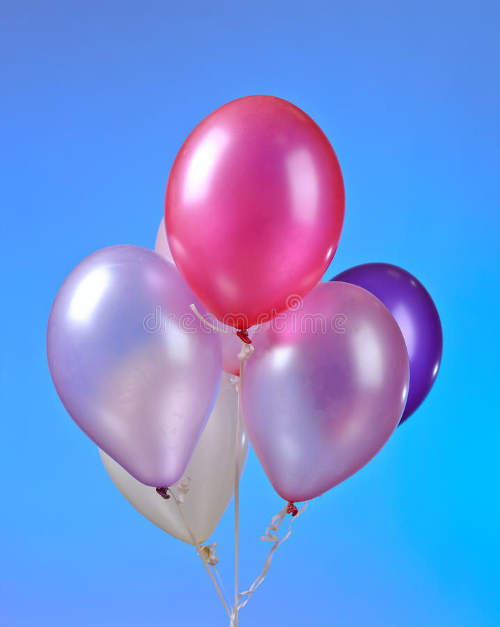 Colored balloons on a blue background. A bunch of colored balloons on a blue background royalty free stock photography
