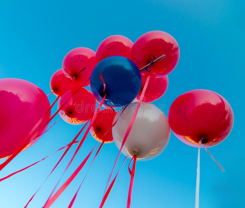 Colored balloons in the blue sky. Many colorful balloons launched from the children happy flying in the blue sky royalty free stock image
