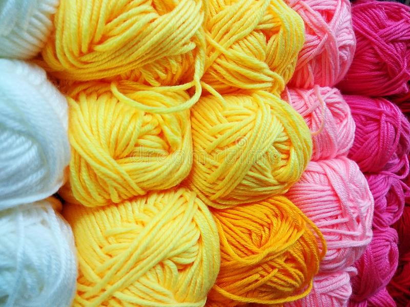 Variegated, bright and colorful yarns for knitting on shop shelf partially out of focus royalty free stock image