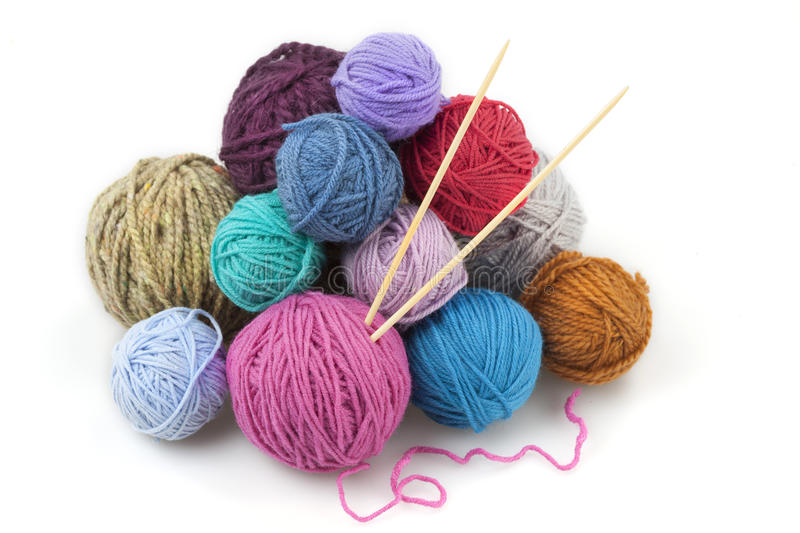 Colored balls of yarn with two knitting needles stock photography