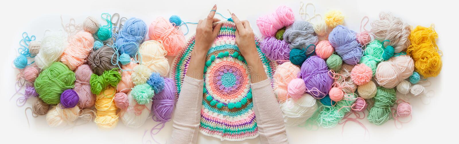 Female hands knitting round mandala with color wool, on a white background, top view. Colored balls of yarn. View from above. Rainbow colors. All colors. Yarn stock illustration