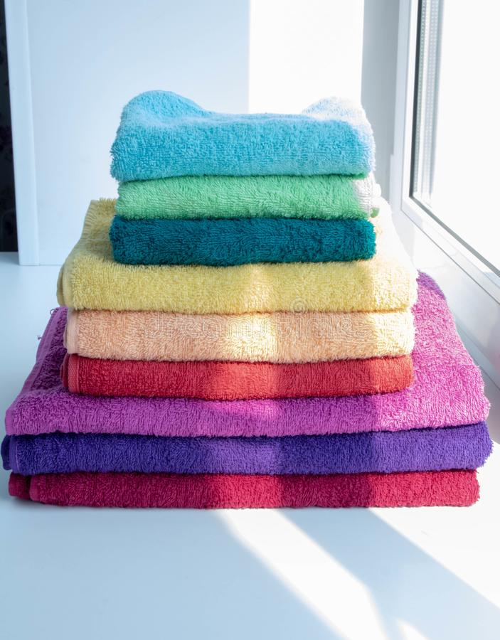 Colored bath towels lie on the window stock image