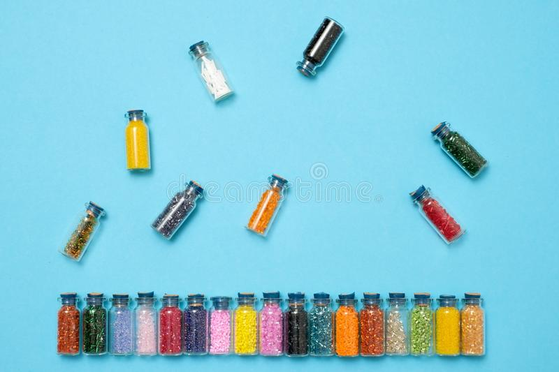 Colored beads in special glass jars. Female or kids hobby royalty free stock images