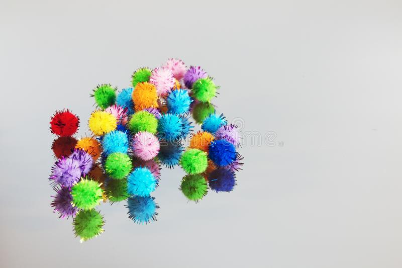 Colored beautiful pompons on a gray background royalty free stock photo