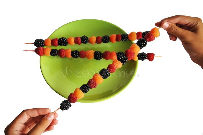 Colored berries impaled on a wooden stick in hand stock images