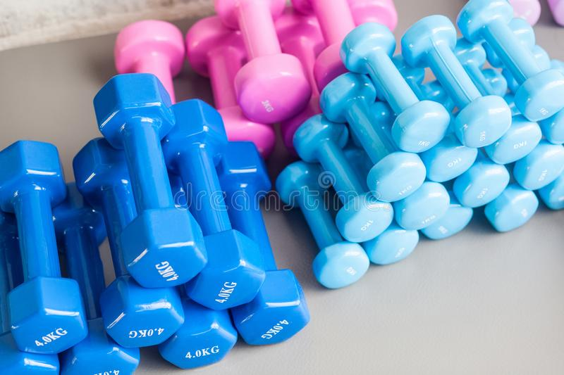 Colored blue and pink dumbbells lie on the gray floor. stock image