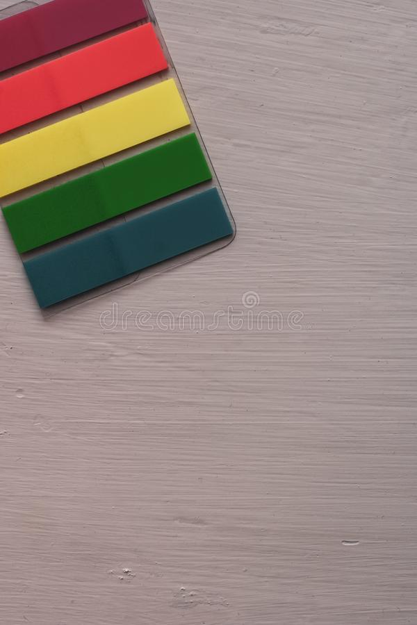 Colored bookmarks lie diagonally on the table. Stripe stickers. Flat lay. Red, yellow, green, blue. Copy space stock photo