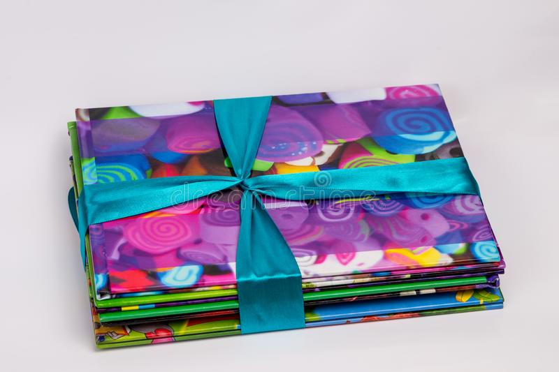 Colored books in a stack. Children`s books in a gift ribbon. Bright colorful little books for children. stock images