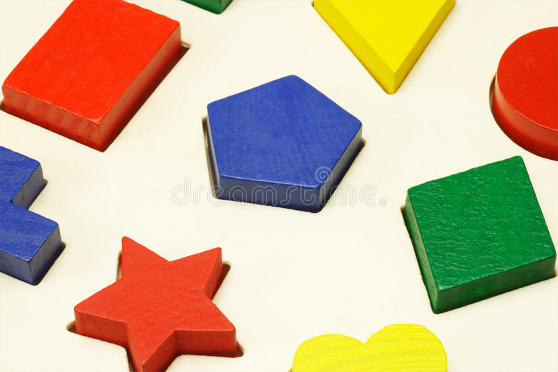 Colored building blocks. Assorted colored building blocks in correct shape holes stock photos