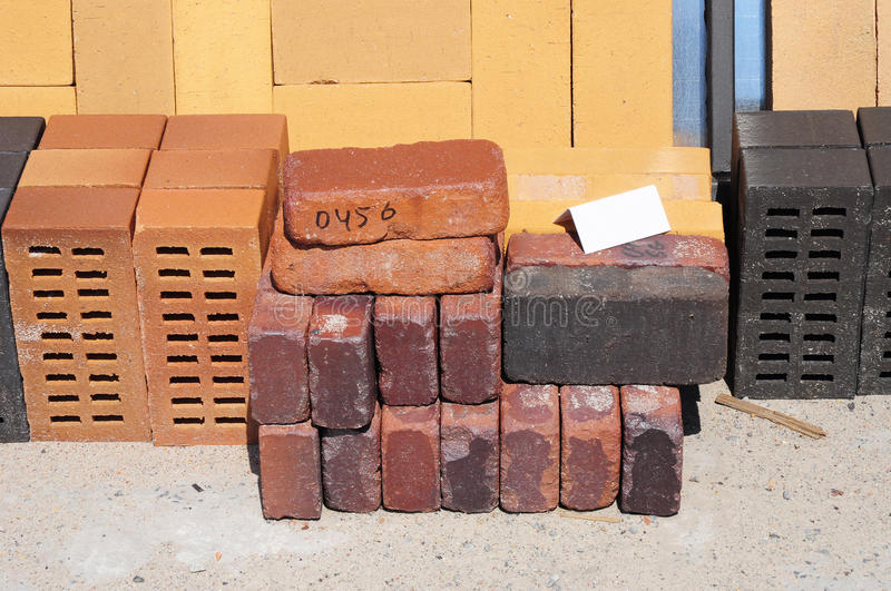 Colored building blocks, bricks and concrete pavers (paving stone) or patio blocks organized on pallets for sale. Stored on metal shelves outdoors stock images