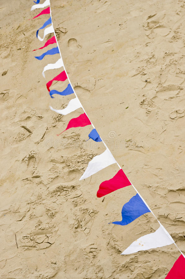 Colored bunting flags on sand surface royalty free stock images