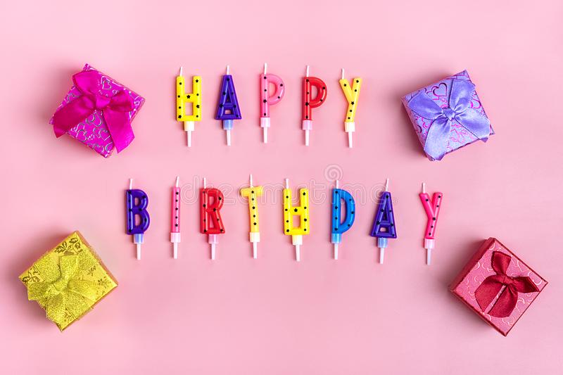 Colored candles on cake in the form of letters happy birthday, gift boxes on pink background stock images