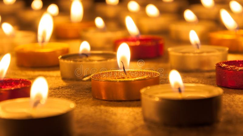 Colored candles lighted. With blurred background on dark background stock photos