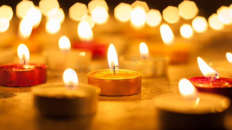 Colored candles lighted. With blurred background on dark background stock image