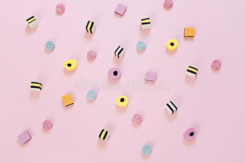 Colored candy scattered on the pink background royalty free stock images