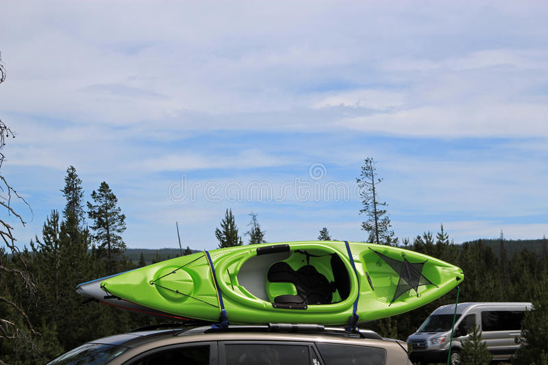 Colored canoe on top of a car. Colored canoe strapped to a roof rack on top of a car royalty free stock photo