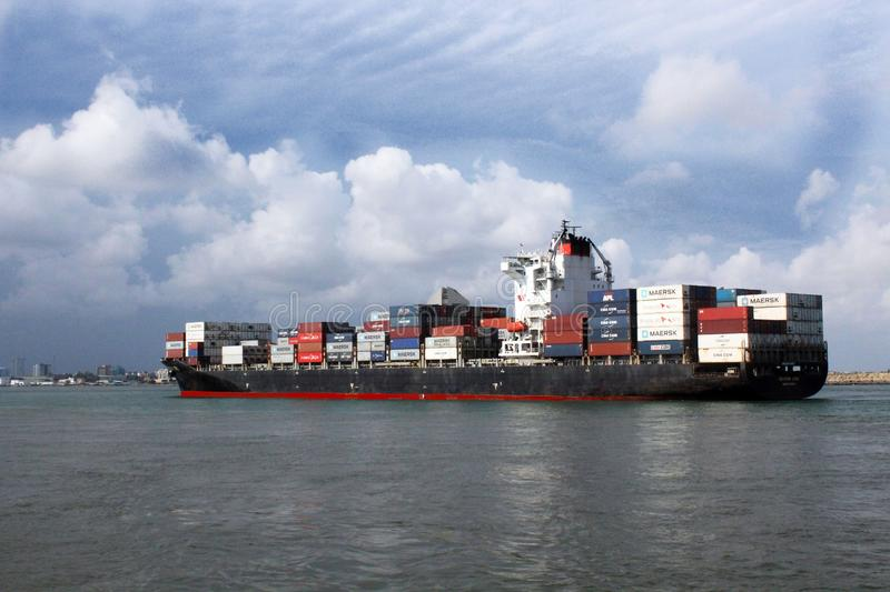 A colored cargo ship loaded with containers  is about to berth at Apapa. A colorful cargo ship arrives Lagos port. The ship is set in Lagos Lanscape setting with royalty free stock image