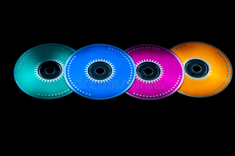 Colored cdrom on black background. Closeup of  four colored cdrom on black background, audio, backup, cd-rom, circle, close-up, compact, computer, data, disc royalty free stock image