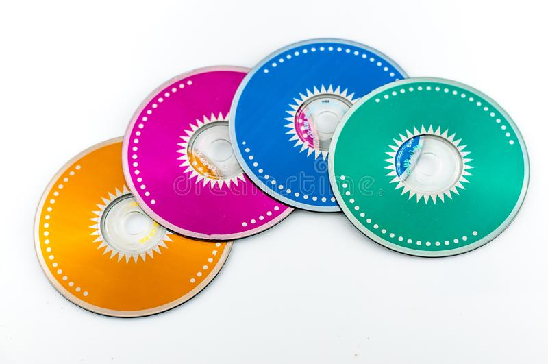 Colored cdrom on white background. Closeup of  four colored cdrom on white background, audio, backup, cd-rom, circle, close-up, compact, computer, data, disc royalty free stock images