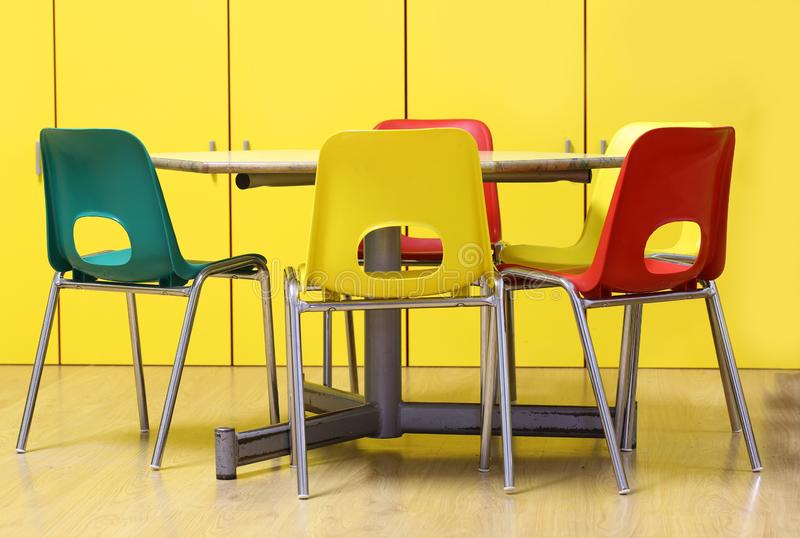 Colored chairs around a table in a nursery school royalty free stock photo