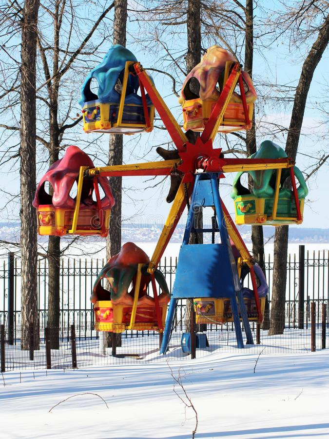 Colored children`s carousel wheel in winter Park royalty free stock photography