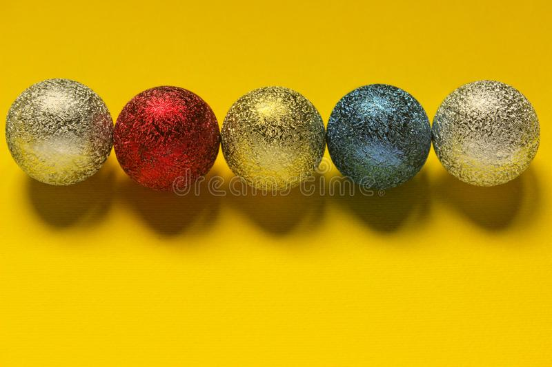 Colored Christmas decoration ball on a yellow background with space for text. stock photography