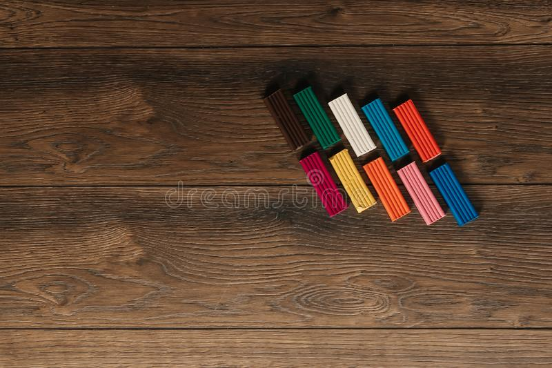 Colored clay lies on a wooden brown table. Copy space.  royalty free stock photos