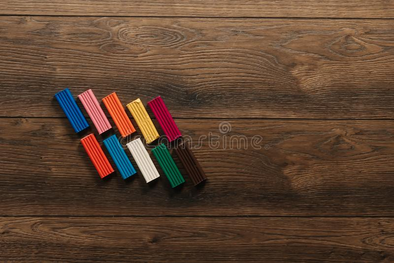 Colored clay lies on a wooden brown table. Copy space.  royalty free stock images