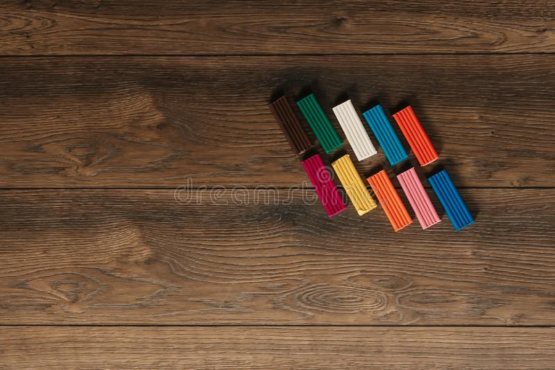 Colored clay lies on a wooden brown table. Copy space.  royalty free stock image