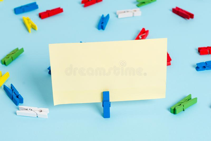 Colored clothespin placed around the empty rectangle square shaped reminder note in the centre of a blue background. Colored clothespin papers empty reminder royalty free stock photo