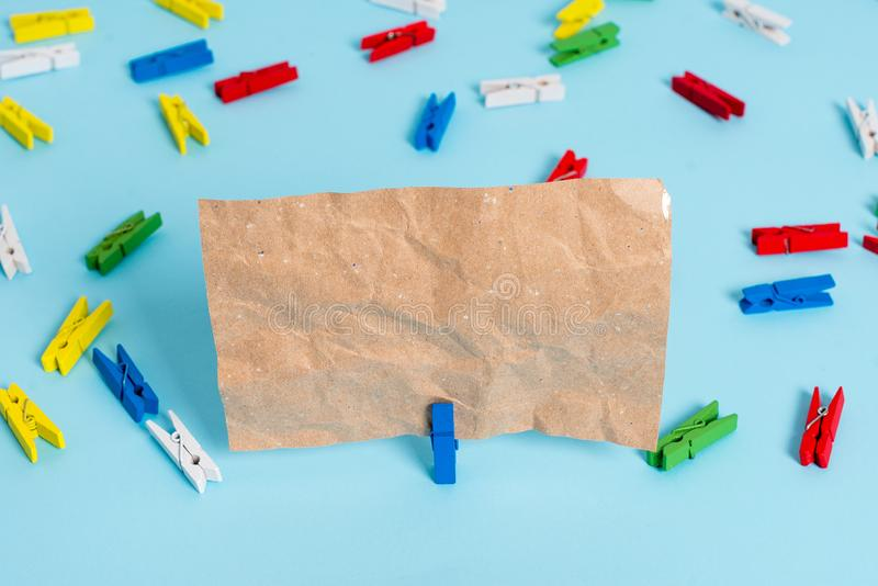 Colored clothespin placed around the empty rectangle square shaped reminder note in the centre of a blue background. Colored clothespin papers empty reminder stock photography