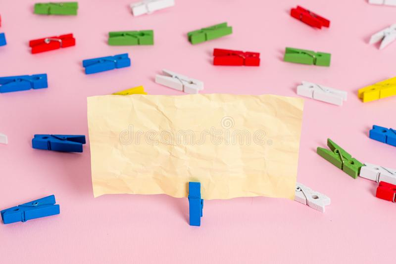 Colored clothespin placed around the empty rectangle square shaped reminder note in the centre of a pink background. Colored clothespin papers empty reminder stock photo