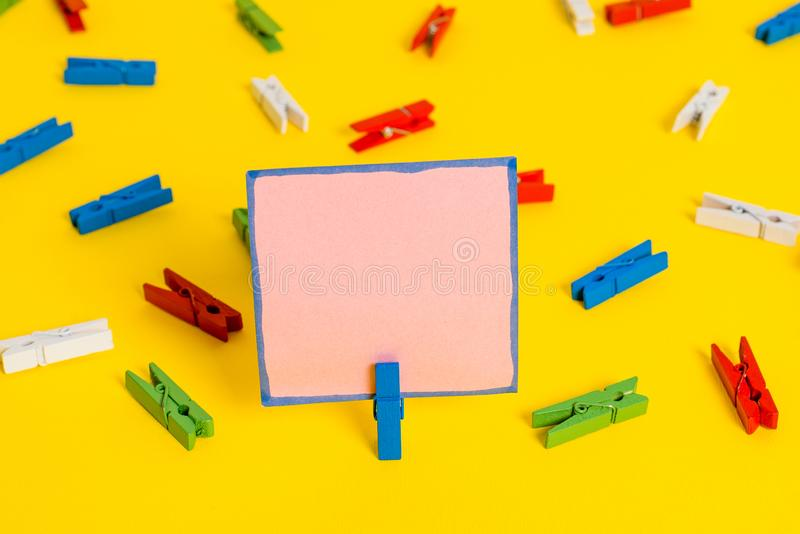 Colored clothespin placed around the empty rectangle square shaped reminder note in the centre of a yellow background. Colored clothespin papers empty reminder royalty free stock images