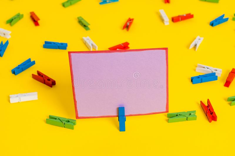 Colored clothespin placed around the empty rectangle square shaped reminder note in the centre of a yellow background. Colored clothespin papers empty reminder stock image