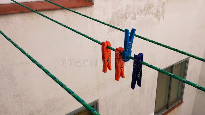 Colored clothespins on the rope stock photo