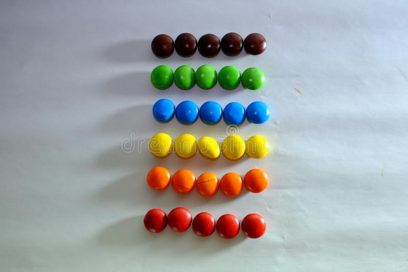 Colored coated chocolate candy similar to m & ms on a white background. Colored coated chocolate candy similar to m&ms on a white background stock photo