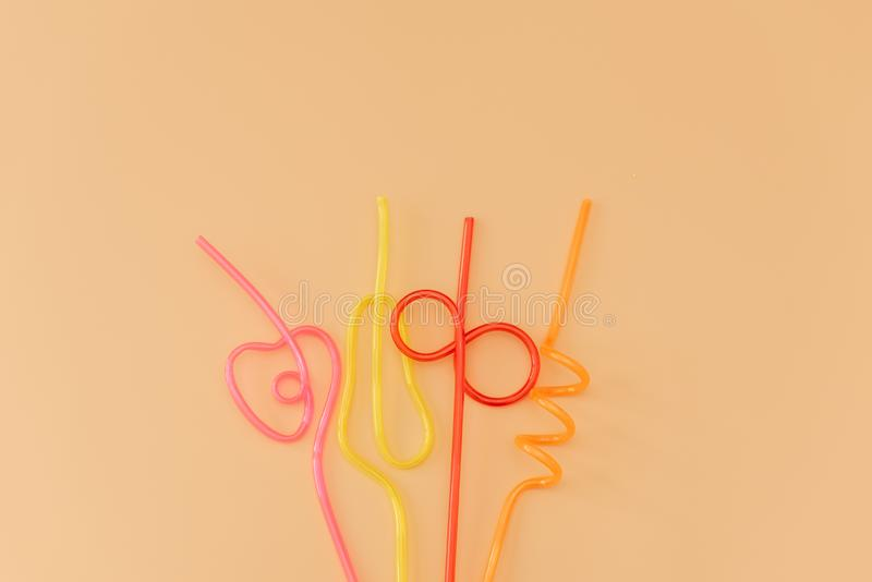 Colored cocktail straws on an orange background stock photos