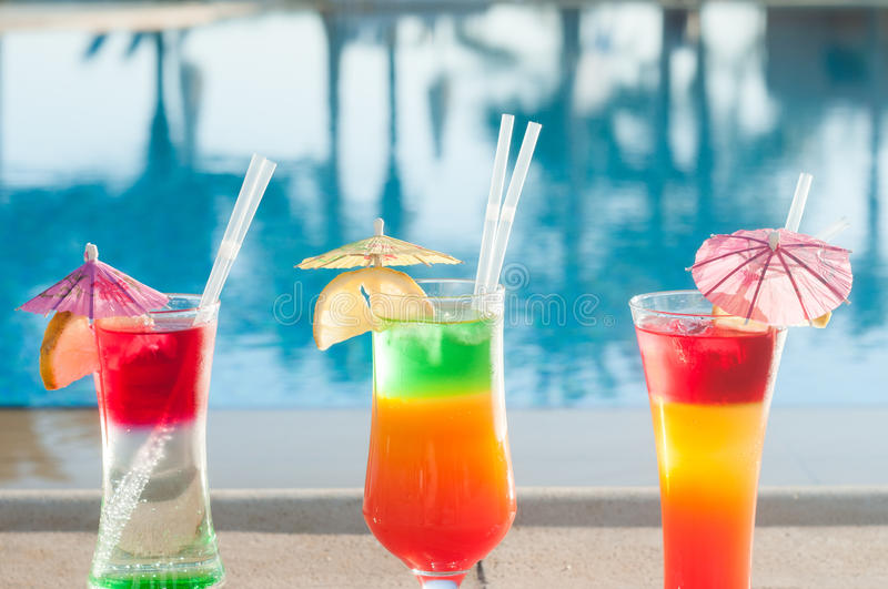 Colored cocktails on a background of water. Colorful cocktails near the pool. Beach party. Summer drinks. Exotic drinks. Glasses of cocktails on table near stock image