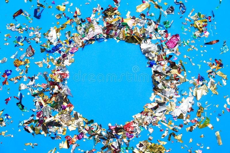Colored confetti flying on blue background. Festive party or carnival border of coiled streamers and confetti on a light blue green wood background with copy stock photography