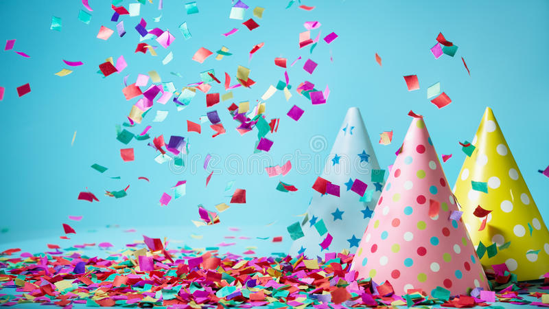 Colored confetti on party hat. Colored confetti and party hat on blue background stock photo