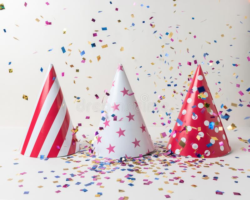Colored confetti and party hat on white background. Minimal party concept royalty free stock image
