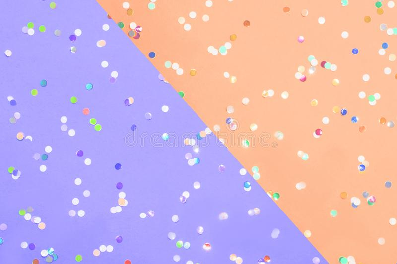 Colored confetti scattered on Colored confetti scattered on purple pastel paperand yellow pastel paper. Colored confetti scattered on purple pastel paper and stock image