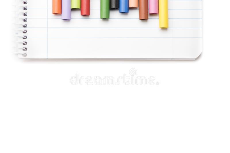 Colored crayons on notebook and white background top view. Group of colored crayons on white background stock photography