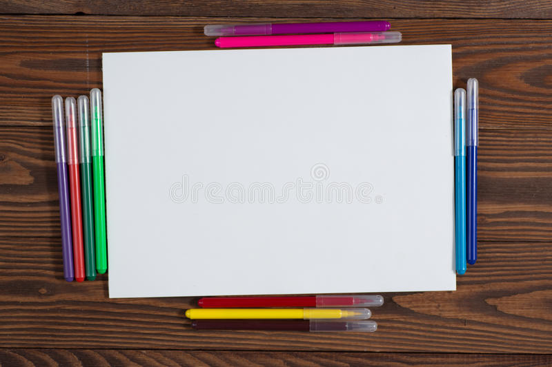 Colored crayons and a sheet of paper notebook wood stock photography