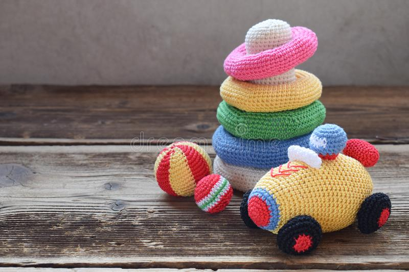 Colored crochet racing car and pyramid from colored rings. Toy for babies and toddlers to learn mechanical skills and colors. Handmade crafts. DIY concept baby royalty free stock photography