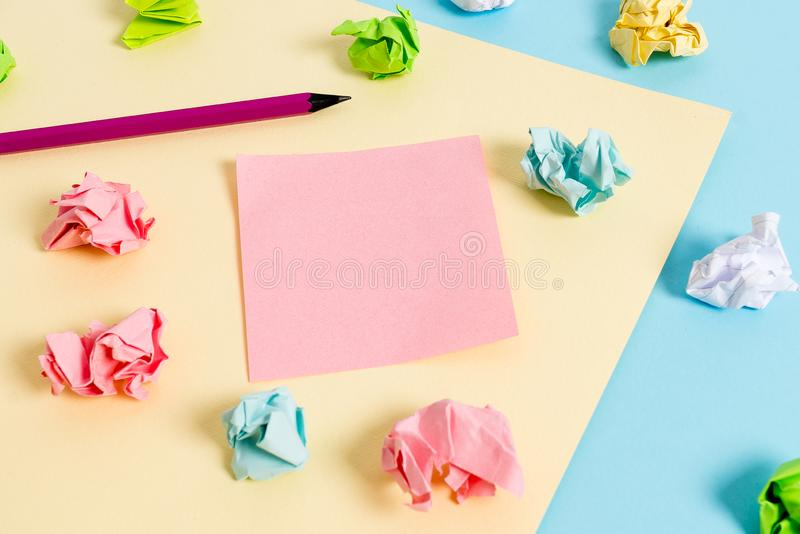 Colored crumpled sheets and a pencil placed around the empty rectangle shaped reminder note in the centre of a blue. Colored crumpled papers empty reminder blue royalty free stock images