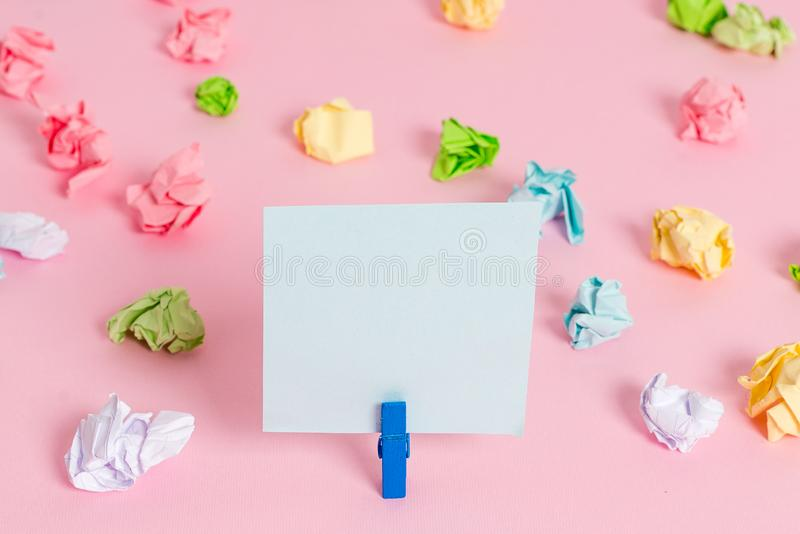 Colored crumpled sheets placed around the empty rectangle square shaped reminder note in the pink background. Office. Colored crumpled papers empty reminder pink royalty free stock image