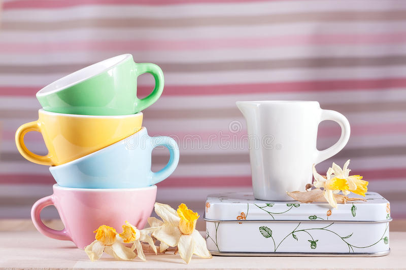 Colored cups with a pitcher and daffodils vintage retro royalty free stock images